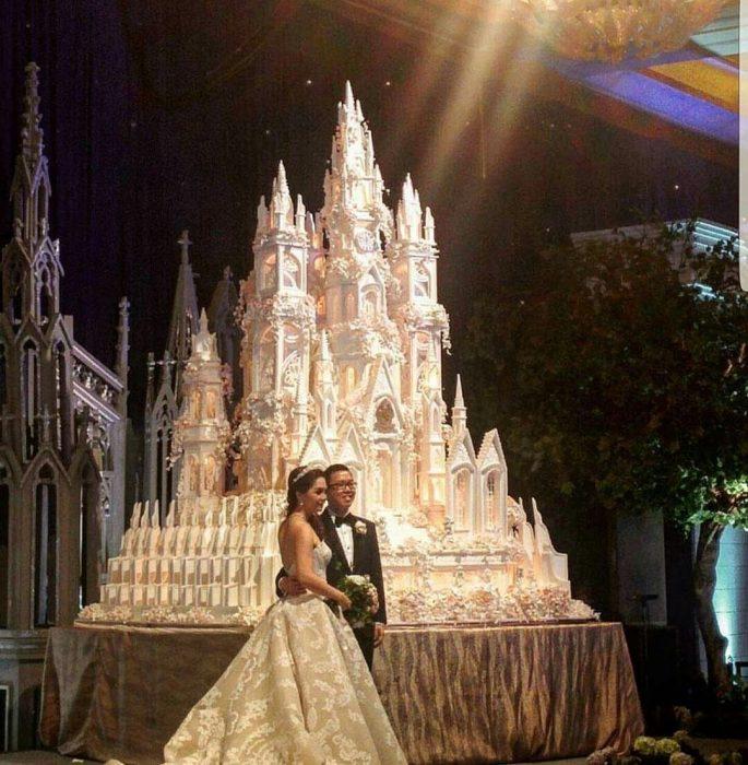 Pareja de novios parados frente a un pastel de bodas impresionante en forma de castillo