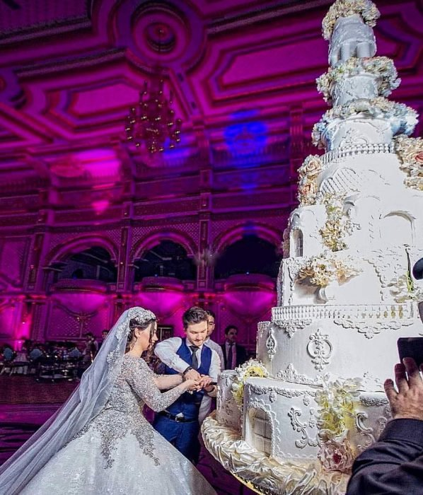Pareja de novios el día de su boda partiendo un pastel de boda con 8 pisos, de color blanco, con flores de azúcar y decoraciones con betún