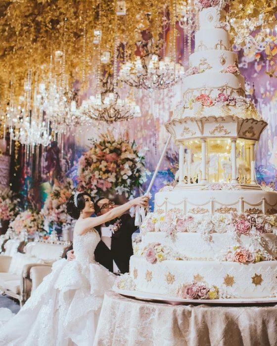 Pareja de novios el día de su boda cortando un enorme pastel de 9 pisos de color blanco y decorado con rosas