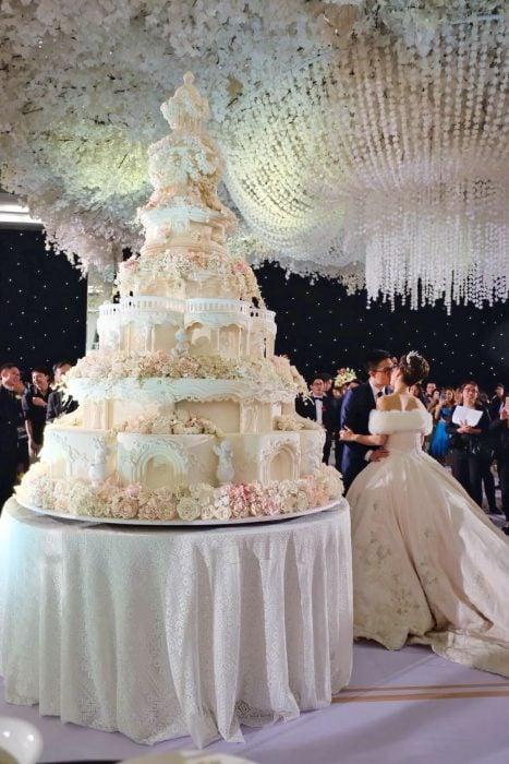 Pareja de novios parados frente a un enorme pastel de bodas