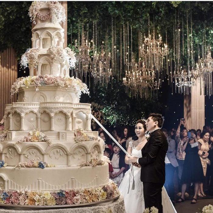 Novios sujetando una espada para cortar su pastel de bodas de 8 pisos decorado con betún blanco y flores de azúcar de diferentes colores