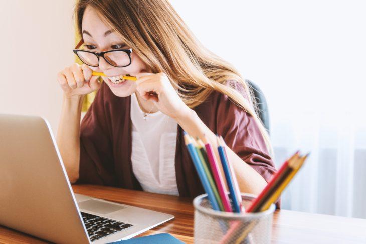 Mujer mordiendo lapiz frente a computadora