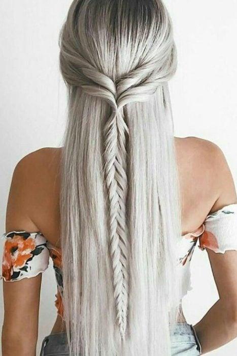 Chica parada de espaldas mostrando su trenza cola de pez con cabello suelto