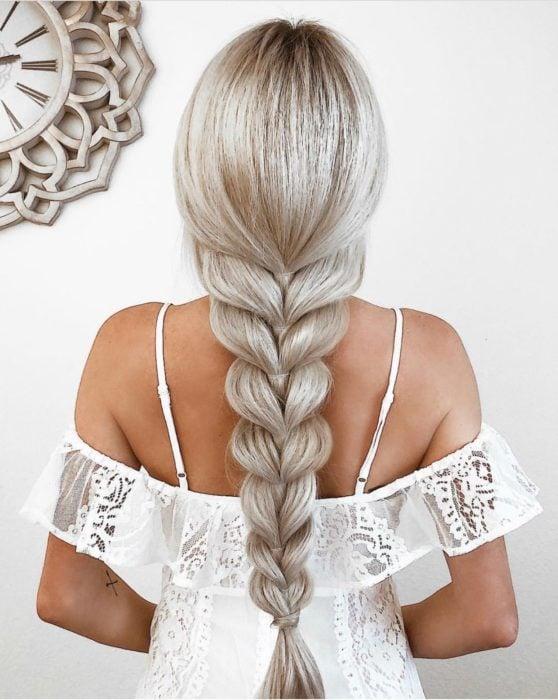 Chica parada de espaldas mostrando su trenza y cabello platinado