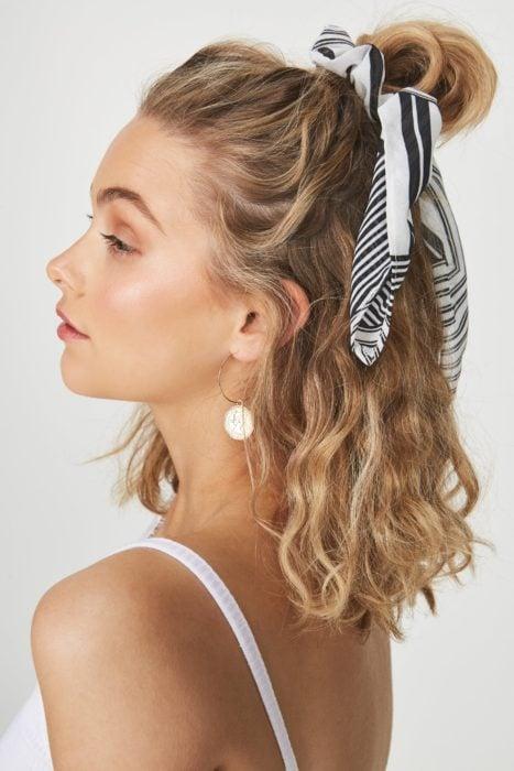 Ideas de peinados para el calor; mujer de perfil con cabello corto, chino y rubio, agarrado en media cola alta con un paliacate rayado