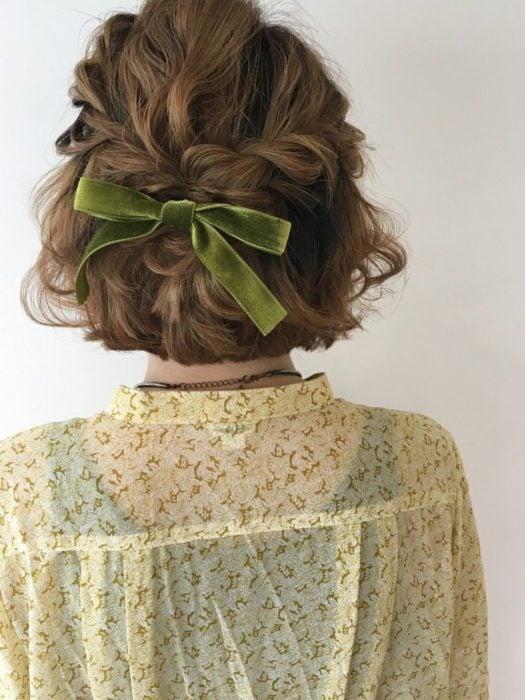 Ideas de peinados para el calor; chica de españdas de cabello castaño, ondulado y corto, con peinado de trenza y media cola, con listón verde