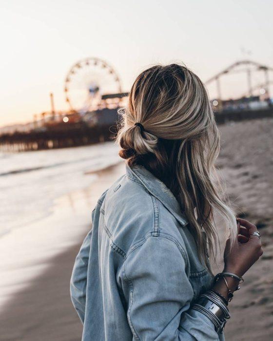 Ideas de peinados para el calor; mujer con cabello rubio ombré, peinada con media cola; en la playa con una rueda de la fortuna en el fondo