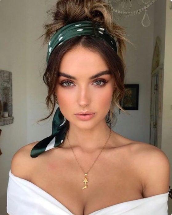 Ideas de peinados para el calor; mujer de ojos verdes con cabello castaño, peinada con un chongo alto y una bandana verde con lunares blancos