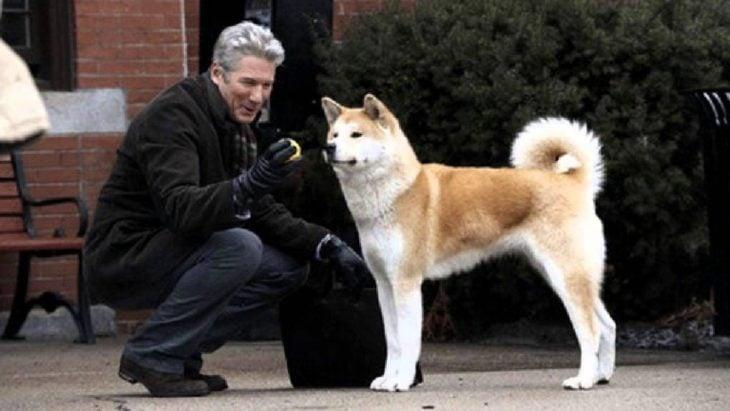 Richard Gere jugando con un perro de raza akita fuera de la estación de tren, escena película Siempre a tu lado: Hachiko