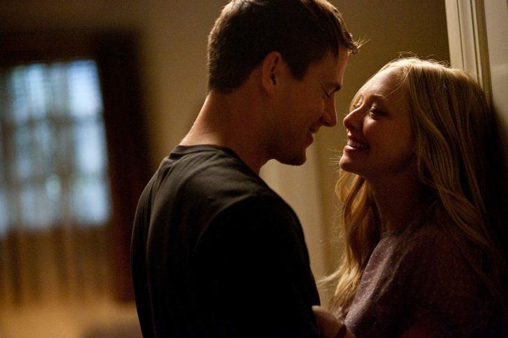 Channing Tatum y Amanda Seyfred dentro de una habitación mirándose de frente y sonriendo, escena de la película Querido John