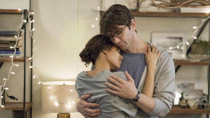 Michiel Huisman y Gugu Mbatha-Raw abrazados dentro de una habitación con luces artificiales, escena de la película Y nadie más que tú