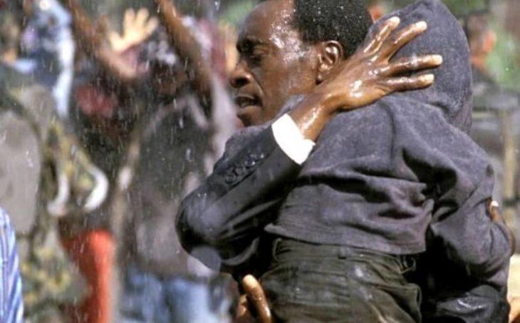 Don Cheadle cargando a un niño y corriendo bajo la lluvia, escena de la película Hotel Rwanda