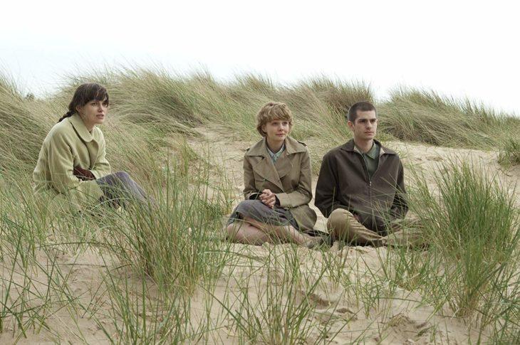 Keira Knightley, Carey Mulligan y Andrew Garfield sentados sobre la tierra seca, escena de la película Nunca me abandones