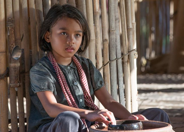 Sareum Srey Moch sentada en el piso recargada en una pared de bambú, escena de la película Se lo llevaron: Recuerdos de una niña de Camboya
