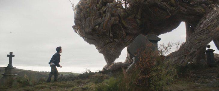 Lewis MacDougall fuera de parque viendo a monstruo creado co CGI, escena de la película Un monstruo viene a verme
