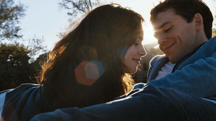 Lily Collins recostada sobre Sam Claffin en un parque sonriendo, escena de la película Love, Rosie
