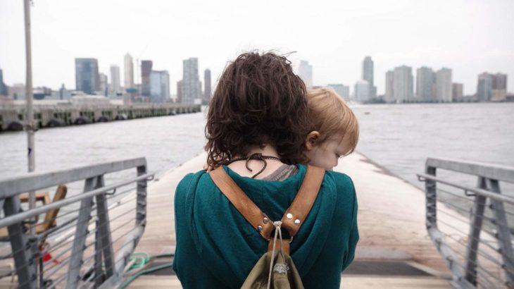 Ellen Page de espaldas cargando a una bebé en brazos sobre un muelle, escena de la película Tallulah