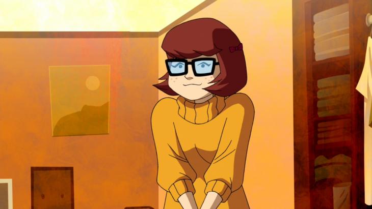 Velma de la caricatura Scooby Doo con los brazos cruzados mientras está parada en una habitación