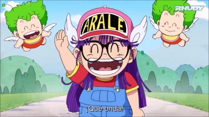 Arale usando su clásico overol y gorra rosa, saludando
