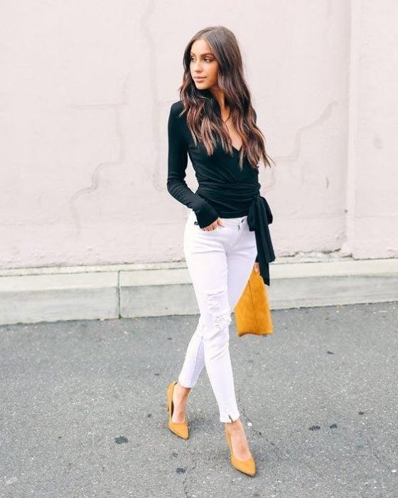 Mujer joven vistiendo pantalón blanco y blusa negra con bolsa amarilla