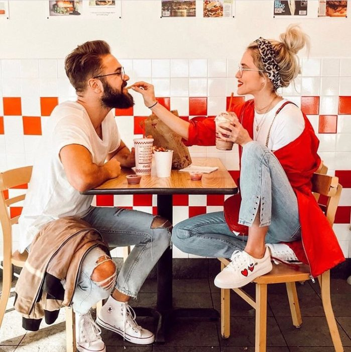 Pareja de novios comiendo papas fritas dentro de un restaurante