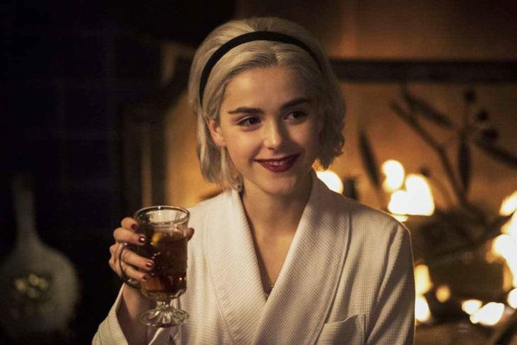 Escena de la serie Sabrina; actriz sosteniendo una copa de vino en la mano mientras sonríe