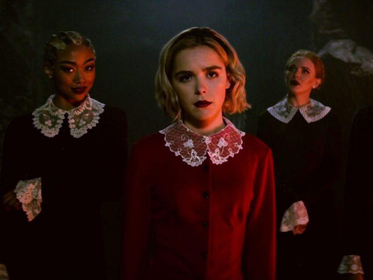 Escena de la serie Sabrina; Actriz que interpreta a Sabrina parada junto a dos de sus rivales mientras usan las batas de su escuela