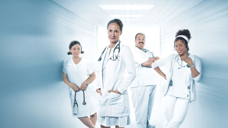 Escena de la serie Getting On. Protagonistas vestidas de doctoras y enfermeras paradas en un pasillo blanco