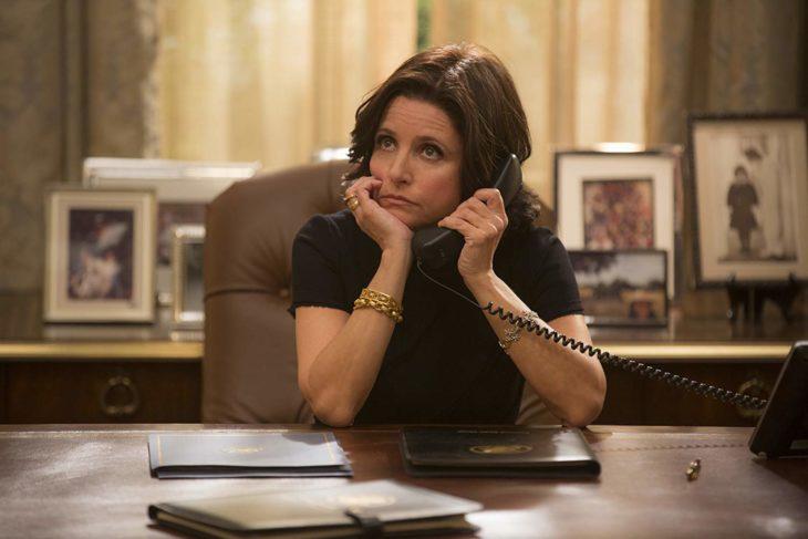Escena de la serie Veep de HBO. Mujer sentada en un escritorio mientras está llamando por teléfono