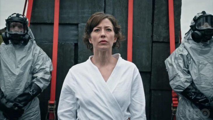 Escena de la serie The Leftovers. Mujer usando una bata blanca parada delante de dos hombres con trajes anti gas