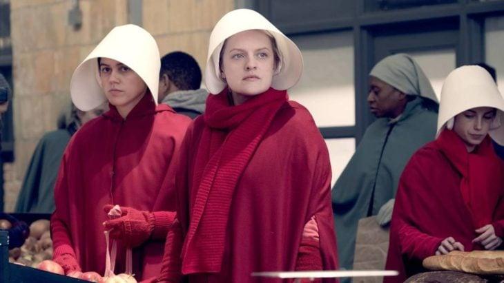 Escena de la serie El cuento de la criada. Mujeres vestidas de rojo y usando un sombrero blanco