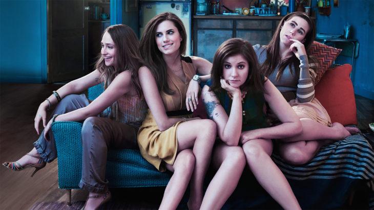 Escena de la serie Girls. Chicas sentadas en un sillón pensando y riendo