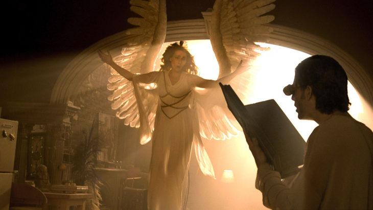 Escena de la serie Ángeles en América. Ángel extendiendo sus alas mientras un hombre la dibuja en un cuaderno
