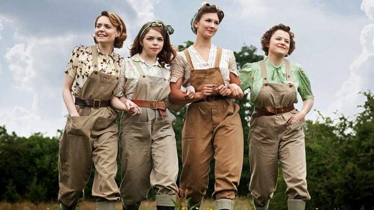 Escena de la serie de Netflix: The Land Girls. Mujeres vistiendo con overoles mientras caminan abrazadas