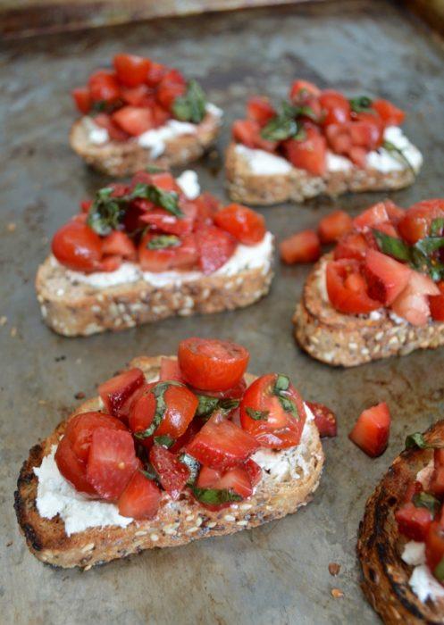 Tostadas gourmet con queso de cabra, rodajas de tomate, y fresas