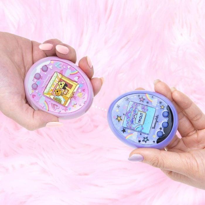 Anuncian regreso de Tamagotchi, la mascota virtual de los noventas; manos sosteniendo un tamagothci rosa y azul