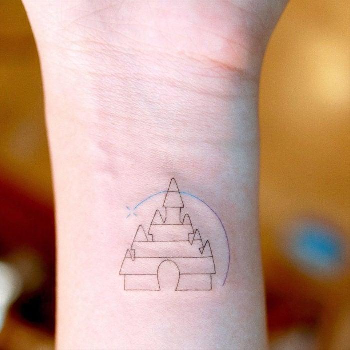 Tatuaje minimalista del castillo de Disney en la muñeca