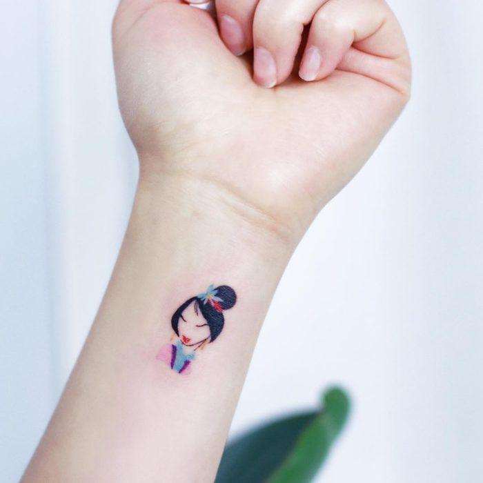 Tatuaje minimalista de Mulán de Disney en la muñeca
