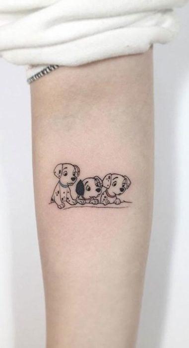 Tatuaje minimalista de 101 dálmatas en el brazo