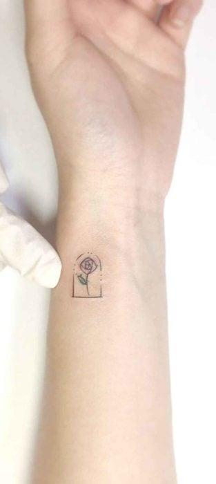 Diseño de tatuaje en el brazo que es la rosa de la Bella y la Bestia