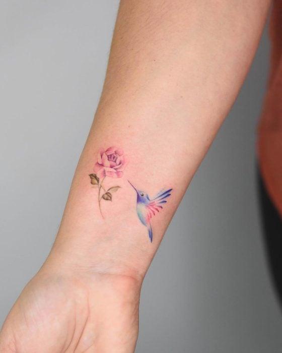 Diseño de tatuaje de colibrí que va a picar una flor