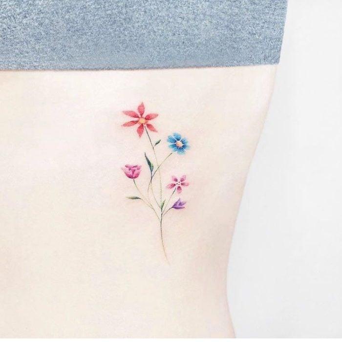 Diseño de tatuaje minimalista de un tallo con diferentes flores