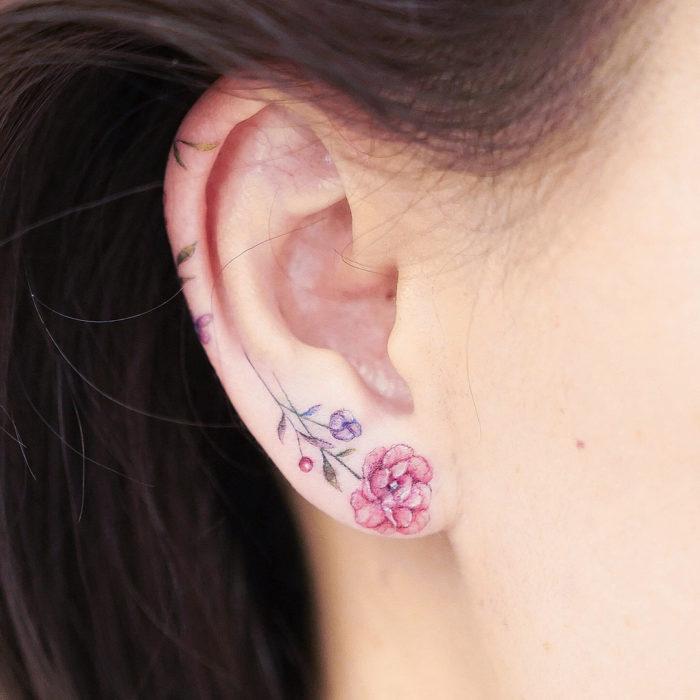 Diseño de tatuaje minimalista de una flor colocada en el lóbulo de la oreja