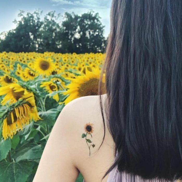 Diseño de un tatuaje minimalista de un girasol colocado en la espalda