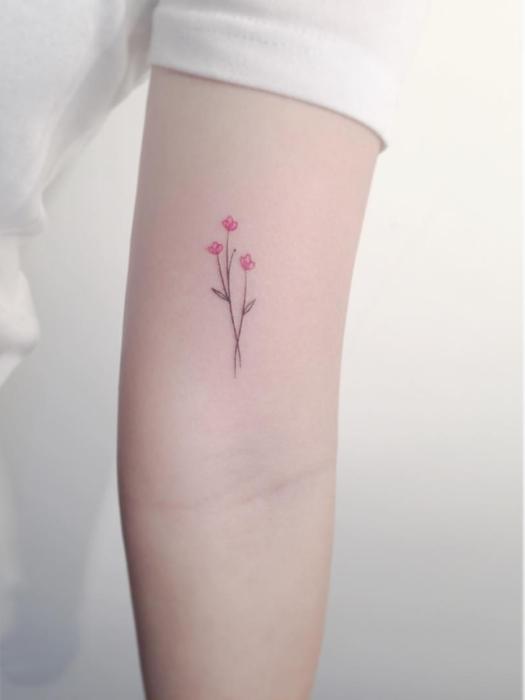 Diseño de tatuaje minimalista que son flores colocadas en el brazo
