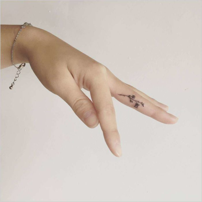 Diseño de tatuaje que es una flor en el dedo