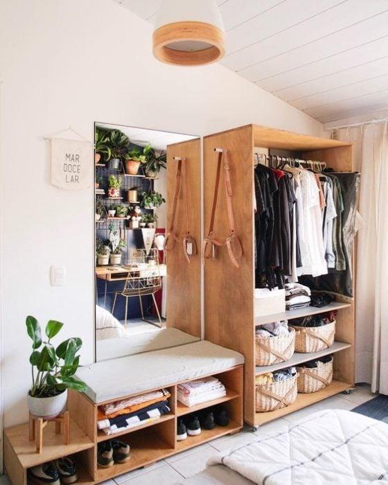 recamara con mesa y closet de madera repleto de ropa