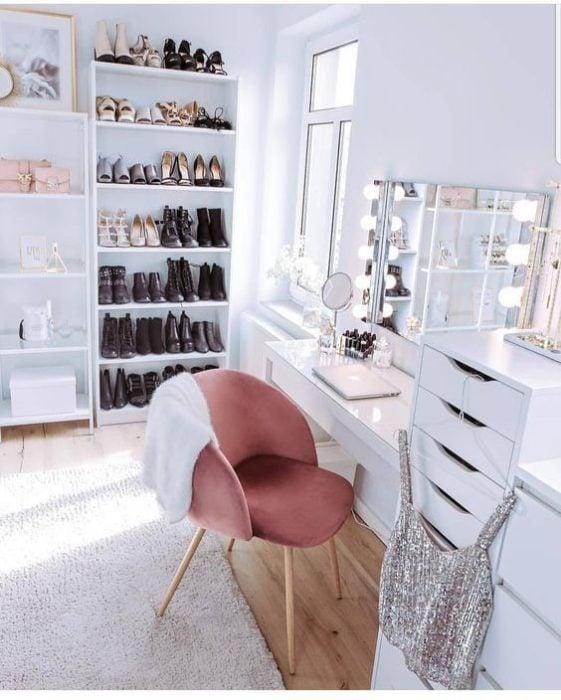 zapatero sin puerta con botas de colores oscuros, frente a un tocador blanco y una silla rosada