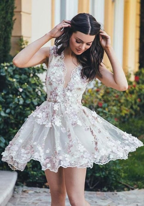 Chica usando un vestido corto en color blanco con aplicaciones florales