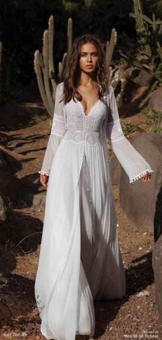 Chica caminando por una vereda desértica usando un vestido de color blanco estilo boho